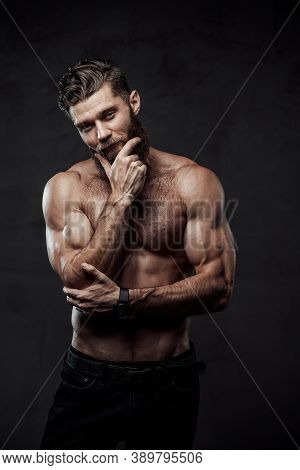 Handsome And Haired Man With Nude Torso And Muscular Build Posing With Hand Under His Chin In Dark B