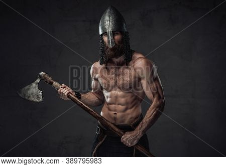 Nord Barbarian With Naked Torso And Beard In Helmet Posing Holding His Two Handed Axe In Dark Studio