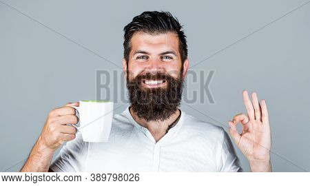 Handsome Man Holds Cup Of Coffee, Tea. Bearded Man Smiling Showing Sign Ok. Good Morning, Man Tea, O