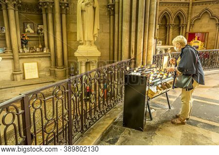 Bayeux, France - September Circa, 2020. Unidentified Senior Woman Lights A Prayer Candle At The Cele
