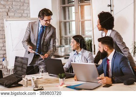 Multi-ethnic Group Of Happy Business People Having A Meeting In Modern Office.