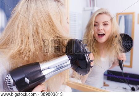 Haircare. Beauty Long Haired Blonde Woman Drying Hair In Bathroom. Smiling Girl Blowing Wind On Wet