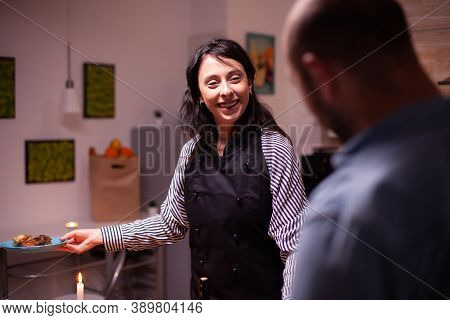 Wife Smiling At Husband Wearing Apron While Looking At Husband After Cooking Tasty Dinner. Woman Coo