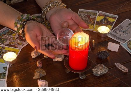 A Fortune Teller Holds A Magic Ball And A Tarot Card With A Heart.the Gypsy Lays Out Tarot Cards And