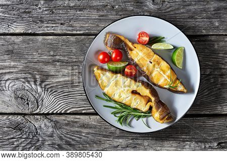 Traditional Wild-caught Smoked Halibut Fish Steaks With Lime, Rosemary Sprigs And Tomatoes On A Plat
