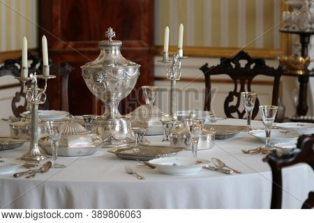 Old Vintage Silver Tableware Set Out On Table With White Tablecloth In Vintage Interior
