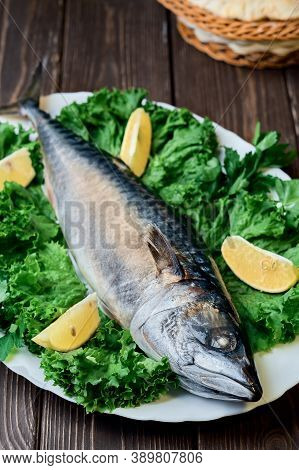Fresh Mackerel Fish On A Platter With Lettuce And Lemon Wedges, Ingredients For Cooking Fish. Close-