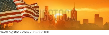 American flag concept. USA Flag over sunrise sun peaking behind city of Los Angeles skyline in background.