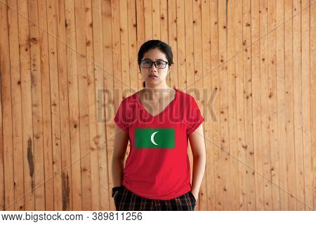 Woman Wearing Maldives Flag Color Shirt And Standing With Two Hands In Pant Pockets On The Wooden Wa
