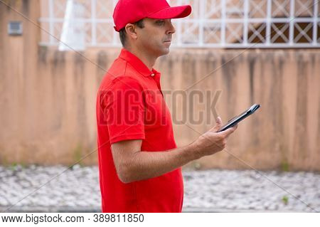 Thoughtful Man Holding Tablet, Standing And Looking Away. Cropped Side View Of Caucasian Courier In