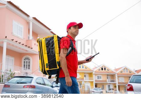Confident Courier Going On Road, Delivering Order And Working On Post. Middle-aged Deliveryman Weari