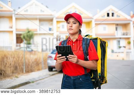 Confident Female Courier Delivering Order And Holding Tablet. Deliverywoman Wearing Jeans, Red Cap A
