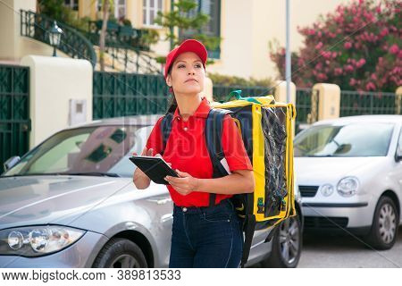 Young Female Courier Looking For House And Holding Tablet. Pensive Deliverywoman Wearing Red Cap And