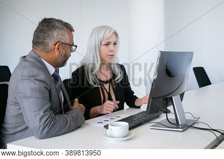 Mentor Helping Intern At Workplace. Colleagues Watching Content On Pc Monitor, Sitting At Table With