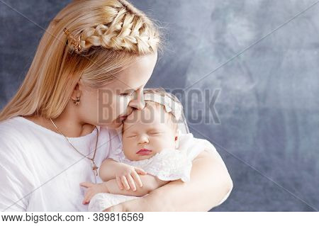 Pretty Woman Holding A Newborn Baby Girl In Her Arms. Happy Mother Kissing Her Slipping Newborn Baby