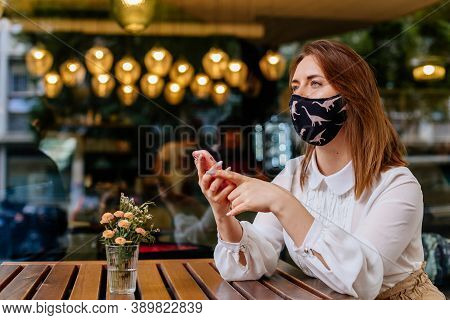 Casual Caucasian Business Woman Wearing Protective Mask Using Phone For Remotely Works Online In Caf