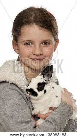 Young girl holding a Dalmatian rabbit against white background