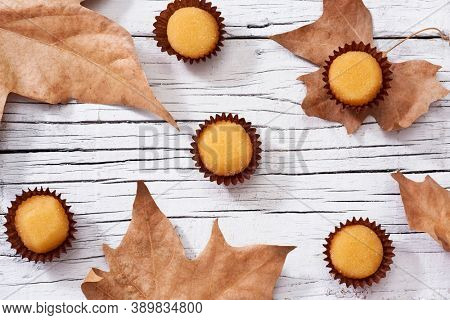 high angle view of some yemas de Santa Teresa or yemas de Avila, a confection typical of Spain, and some autumn leaves on a white rustic wooden surface