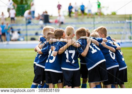 Boys Football Team Forming Huddle. Happy Kids In A Sports Team On Grass Pitch. Summer School Soccer
