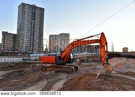 Excavator During Excavation At Construction Site. Backhoe On Road Work. Heavy Construction Equipment