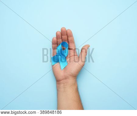 Male Hand Holds Blue Silk Ribbon In The Shape Of A Loop On A Blue Background, Symbol Of The Fight An