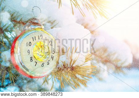 New Year background, New year card -New Year glass Christmas toy in the form of clock showing the New Year Eve, on snowy fir tree branch. New Year festive card, New year toy, New Year background