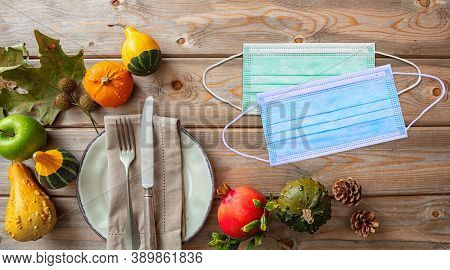 Covid 19 Protective Mask And Thanksgiving Pumpkins Against Wooden Background, Top View
