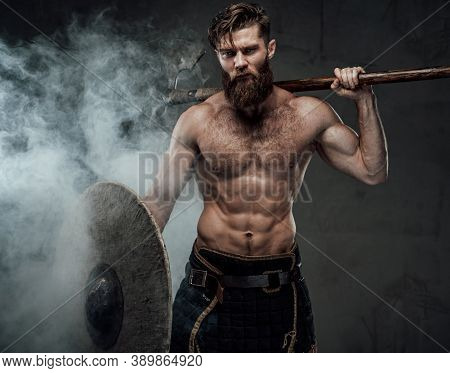Scandinavian Warrior With Beard And Muscular Build Posing Holding His Shield And Axe Behind His Back