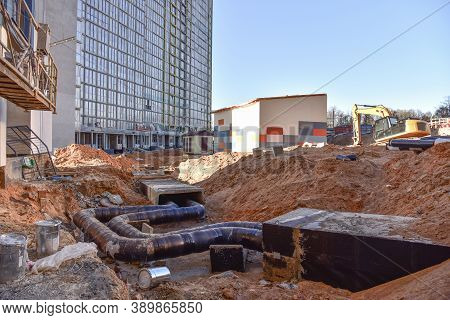 Laying Heating Pipes In A Trench At Construction Site. Install Underground Storm Systems Of Water Ma