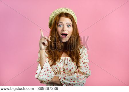 Portrait Of Young Thinking Pondering Woman Having Idea Moment Pointing Finger Up On Pink Studio Back