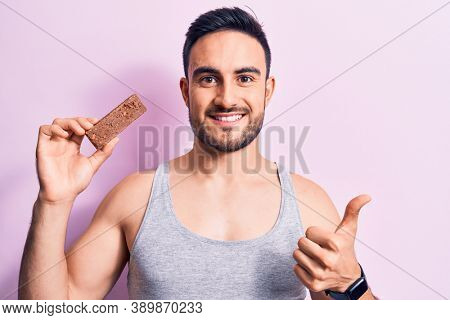 Young handsome man with beard eating energy protein bar over isolated pink background Smiling happy and positive, thumb up doing excellent and approval sign