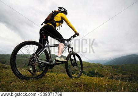 Wide Angle. Young Woman In A Helmet And With A Backpack Stands With A Bicycle Mountains In Cloudy We