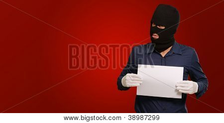 Man wearing a robber mask showing a blank paper on red background