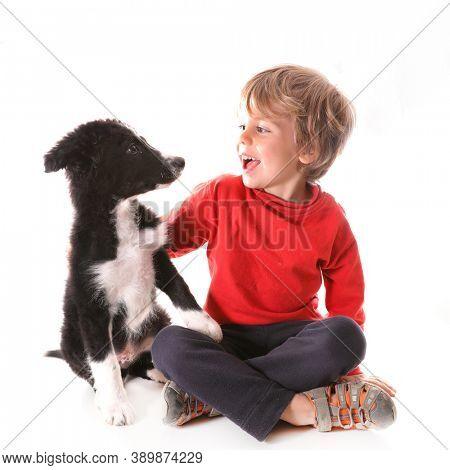 young boy and dog puppy on white background