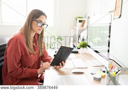 Serious And Confident Freelance Writer Checking Her Notes On A Notepad And Looking Very Busy And Foc