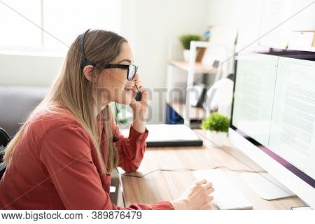 Profile View Of A Woman Working As An Interpreter While Looking At Some Documents And Wearing A Head