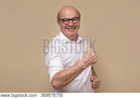 Senior Man Expressing His Excitement And Delight By Shouting Yes