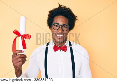 Handsome african american nerd man with afro hair holding graduate degree diploma looking positive and happy standing and smiling with a confident smile showing teeth