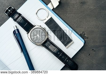 Male Watch And Notepad On Dark Grey Table
