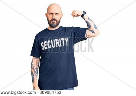 Young handsome man wearing security t shirt strong person showing arm muscle, confident and proud of power