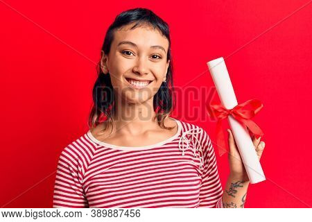 Young woman holding graduate degree diploma looking positive and happy standing and smiling with a confident smile showing teeth