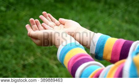 Wet Baby Hands In Rainbow Striped Sleeve Shirt. Kid Plays In Drizzle Catching Droplets In Palms Of H