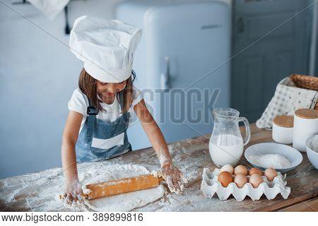 Cute Kid In White Chef Uniform Preparing Food On The Kitchen.