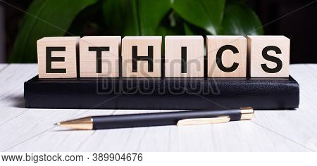 The Word Ethics Is Written On The Wooden Cubes Of The Diary Near The Handle.