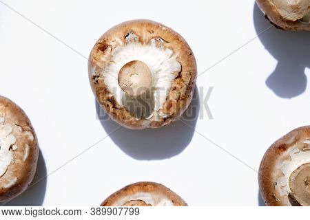 Raw Mushrooms Champignons On A White Background. Mushrooms Upside Down, Top View. Whole Brown Champi