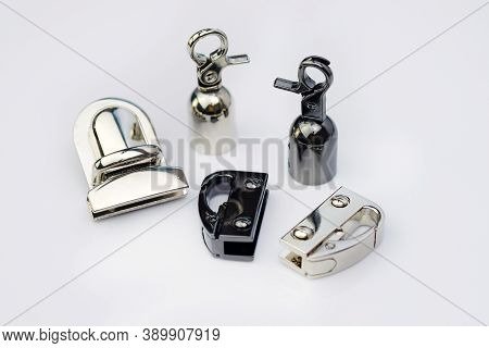Metal Snap Hooks For Bags Of Different Types On A White Background. Lock For A Briefcase And A Woman