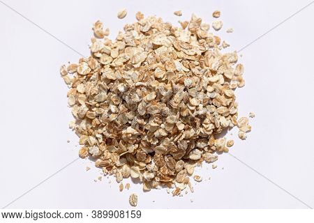 Large oatmeal top view. Raw oatmeal flakes on a white background. Useful grains for a healthy breakfast.