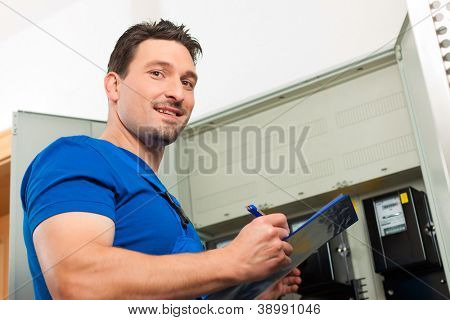 Technician reading the electricity meter to check consumption