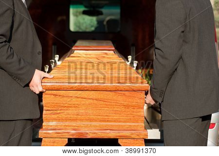 Dolor - Funeral with coffin on a cemetery, the casket carried by coffin bearer