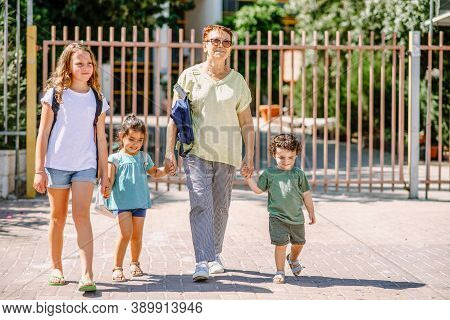 Happy School Children Going To School With Grandmother. Pupils And Grandma With A Backpack Go To Kin